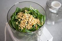 place basil and pine nuts in food processor